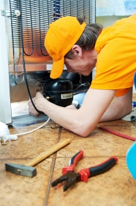Repairman makes refrigerator appliance troubleshooting and maint